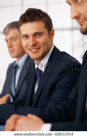 Young businessman sitting with his colleague at the meeting with crossed fingers.