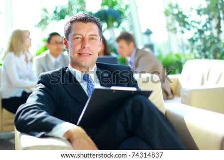 Young businessman smiles towards the camera while his colleagues meet in the backgroun