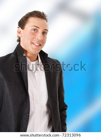 Young businessman smiling. White and blue blurred background.