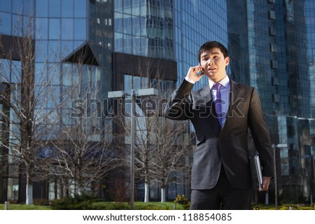Young businessman standing and talking on mobile phone over business center.