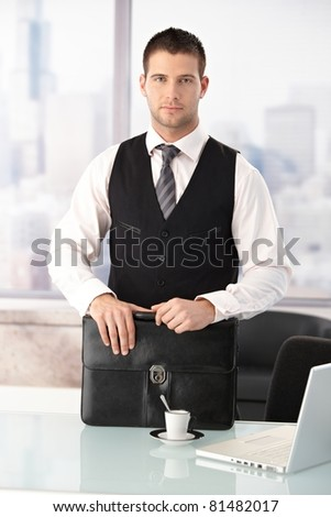 Young businessman standing at desk in bright office.?