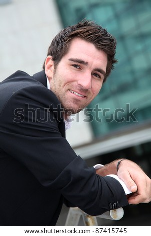 Young businessman standing in front of buildings
