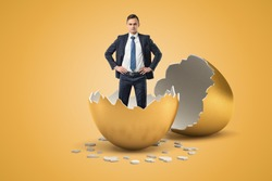 Young businessman standing in golden eggshell as if he just hatched out from egg. New business. Inexperienced businessmen. New ideas.