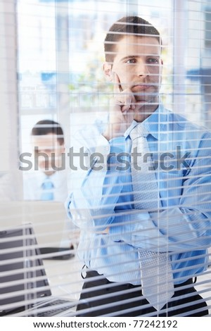 Young businessman standing in modern office, looking through blind, thinking.?