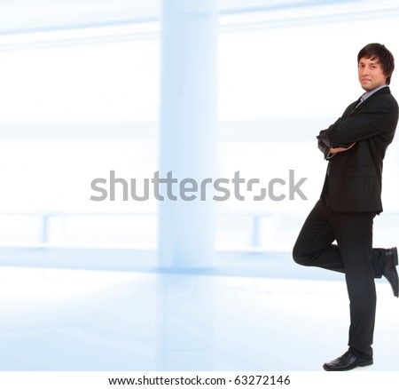 Young businessman standing in office lobby