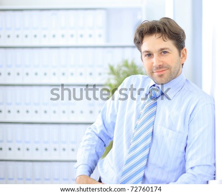 Young businessman standing in office lobby, using smartphone, smiling