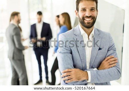 Young businessman standing in the office and other young business people talking in the background