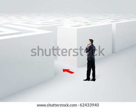 young businessman standing infront of 3d maze - stock photo