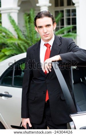 young businessman standing next to his car with doors open