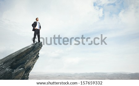 Young businessman standing on a peak