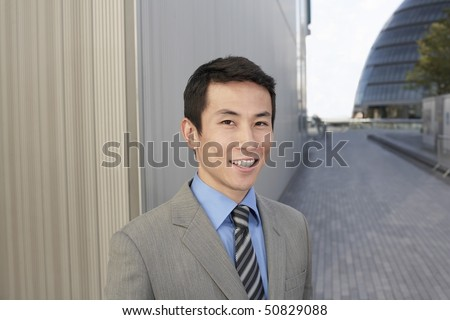 Young Businessman standing outside, smiling