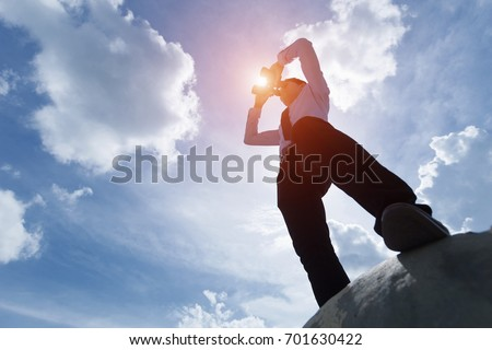 Young businessman standing under the sun and looking through binoculars.