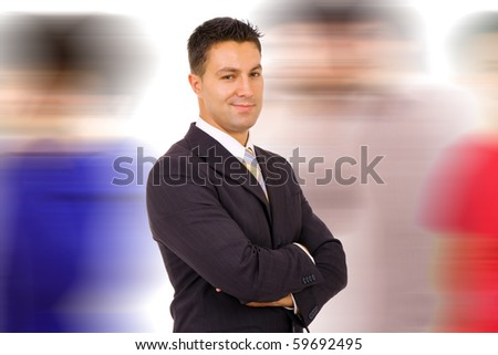 Young businessman standing with armes crossed while others walk by