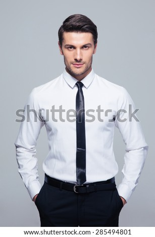 Young businessman standing with hands in pocket over gray background