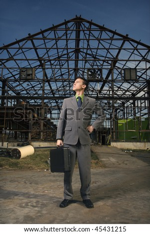 Young businessman stands confidently with a black briefcase in one hand and other hand on his hip. Vertical shot.