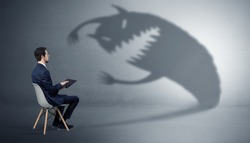 Young businessman staying and negotiate with a monster shadow