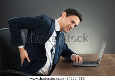 Young businessman suffering from back pain while working on laptop at desk against gray background #342224393