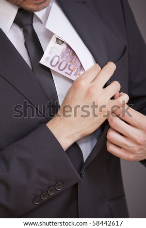 young businessman taking bribe over grey background
