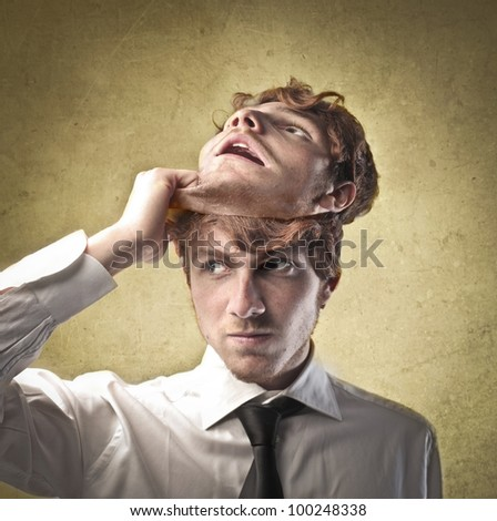 Young businessman taking off a mask