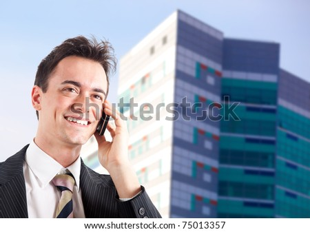 Young businessman talking at the cell phone outdoor