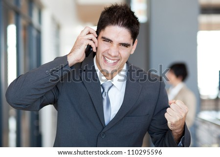 young businessman talking on cell phone and receive exciting news