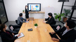 Young businessman talking to his coworkers while analyzing charts during a meeting in board room. All of them are wearing protective face masks due to COVID-19 epidemic.