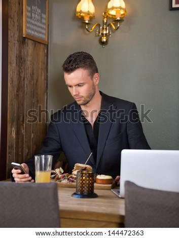 Young businessman text messaging on mobile phone while having meal at cafe
