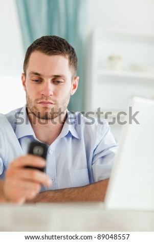 Young businessman texting on his cellphone sitting behind his desk