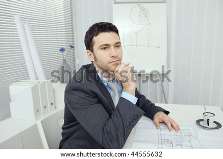 Young businessman thinking over floor plans.