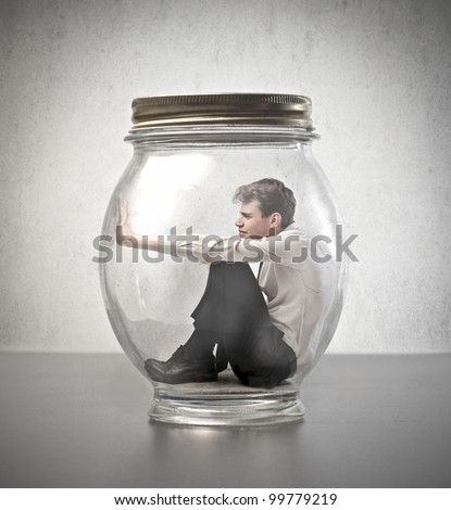 Young businessman trapped in a glass jar