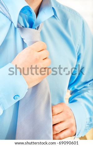 Young businessman tying a tie