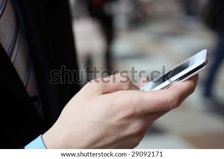 Young businessman typing with cellphone