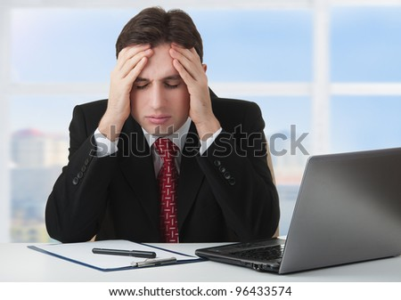 young businessman under stress, fatigue and headache, he kept his hands behind his head