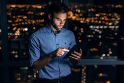 Young businessman using a digital tablet while standing alone in an office late at night in front of windows overlooking the city
