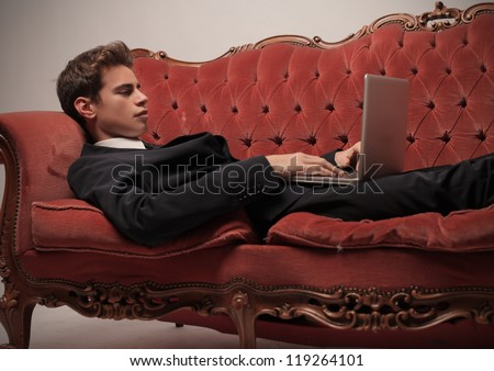 Young businessman using a laptop computer on an antique sofa