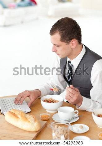 Young businessman using a laptop while having breakfast at home