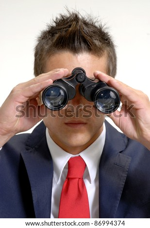 Young businessman using binoculars.