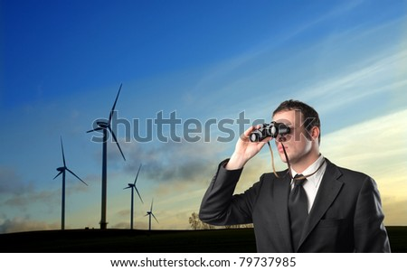 Young businessman using binoculars with windmills in the background