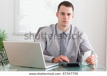 Young businessman using his calculator