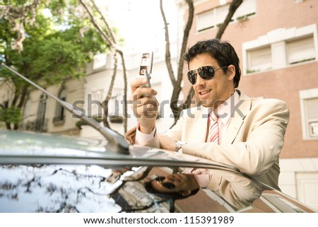 Young businessman using his cell phone while leaning on his car on a tree aligned street.