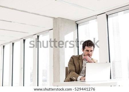 Young businessman using laptop at desk in new office