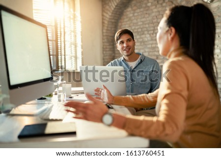 Young businessman using laptop while communicating with female coworker in the office.
