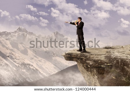 Young businessman using speaker on top of a high mountain