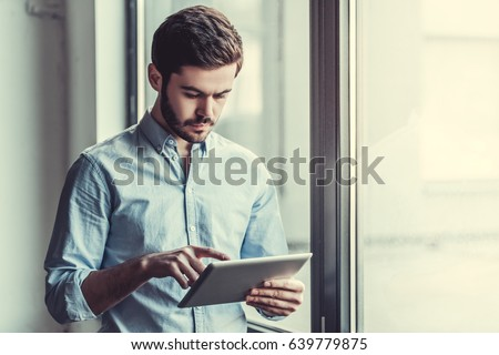 Young businessman using tablet, standing near the window