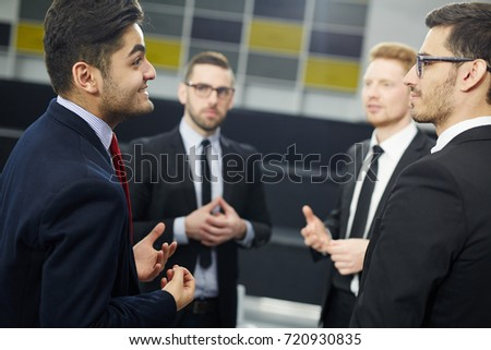 Young businessman voicing his opinion to group of colleagues
