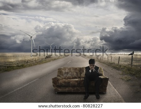 Young businessman waiting on sofa, at the road, disappointed