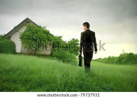 Young businessman walking on a meadow towards an old house