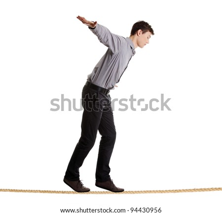 Young businessman walking on rope. Risk in business concept.  Studio shot, isolated on white background. - stock photo