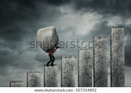 Young businessman walking on the financial chart while carrying a big stone. Concept of hard work #507354892