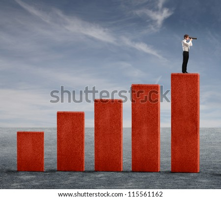 Young businessman watching into a telescope from the top of a business analysis